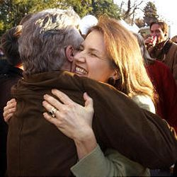 """Lois Smart hugs John Walsh, host of """"America's Most Wanted,"""" before the celebration started Friday night."""