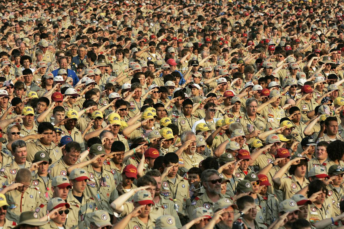 FILE - In this July 31, 2005 file photo, Boy Scouts salute as they recite the Pledge of Allegiance during the Boy Scout Jamboree in Bowling Green, Va. In 2019, financial threats to the Boy Scouts have intensified as multiple states consider adjusting thei