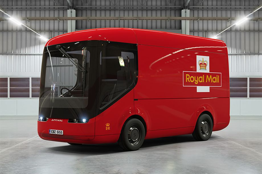 A bright red futuristic-looking delivery truck for the UK's Royal Mail service is seen inside a white warehouse.