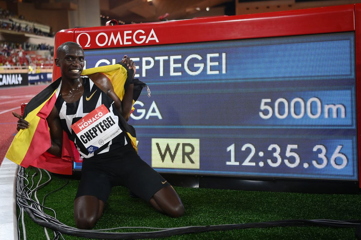 Joshua Cheptegei of Uganda poses for a photo next to a timing board displaying the new 5,000-meter world record.