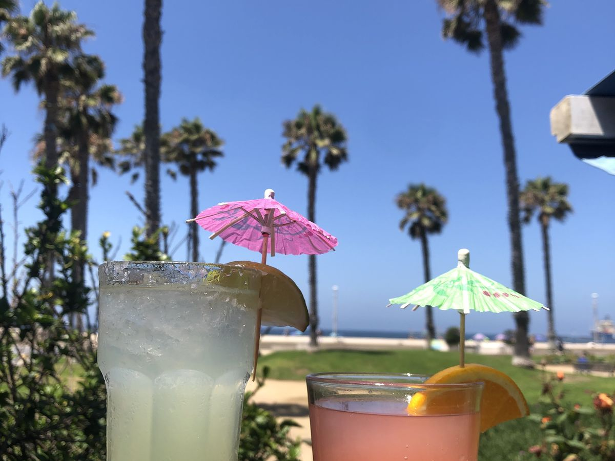 Two colorful cocktails with mini umbrellas and palm trees in the backdrop.