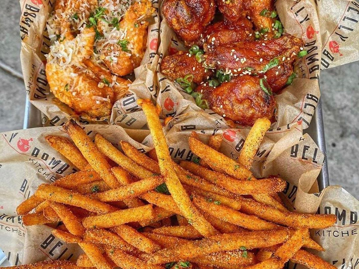 Two different kinds of chicken wings and French fries