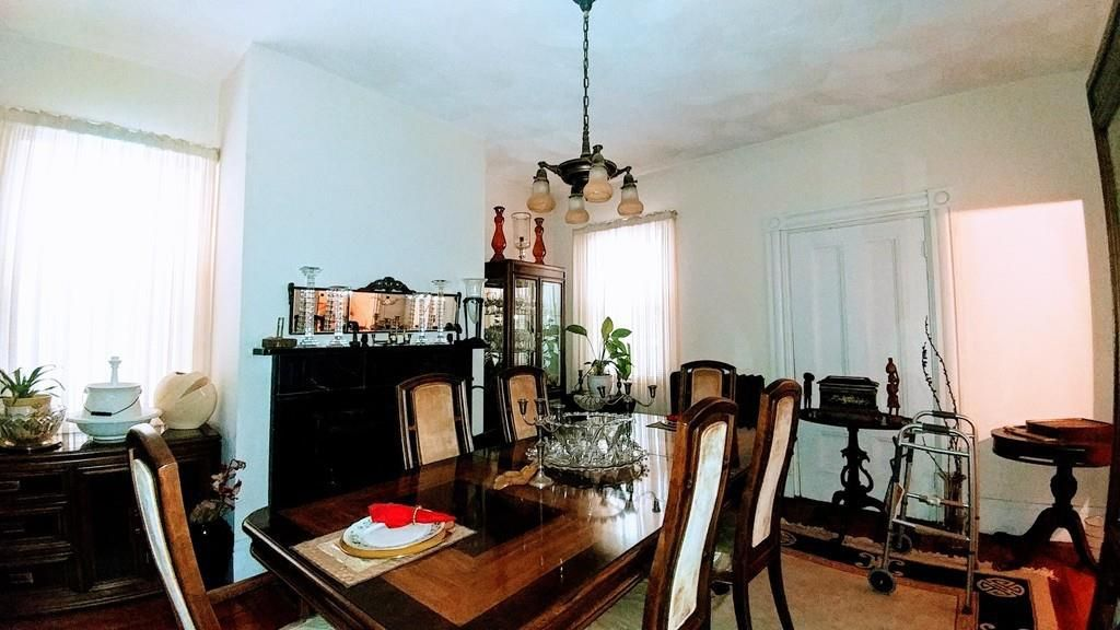 A dining room with a table and chairs.