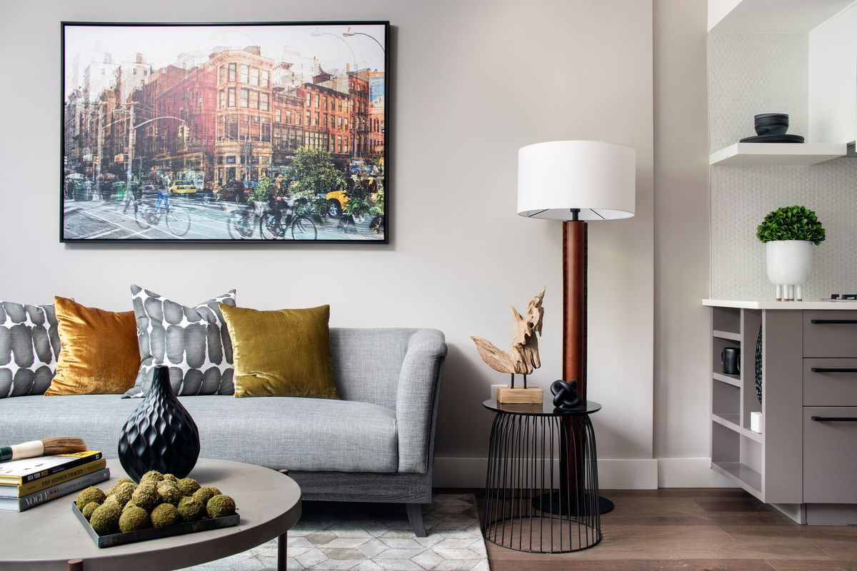 A living area with a grey couch, a framed photo on the wall, a standing lamp, and a coffee table.