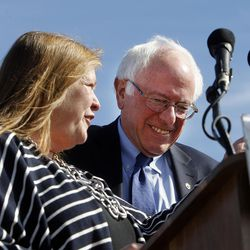 Democratic presidential candidate and Vermont Sen. Bernie Sanders, along with his wife, Jane, left, takes the podium before giving a speech at This is the Place Heritage Park in Salt Lake City, Friday, March 18, 2016.