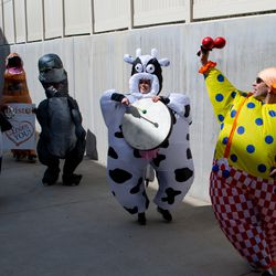 Rachel Cannon, dressed in an inflatable cow costume, Keith Hall, dressed in an inflatable clown costume, and other volunteers with Bristol Hospice Utah play instruments while parading outside of The Ridge Cottonwood, an assisted living facility in Holladay, on Saturday, April 18, 2020. The instruments were provided by DrumBus Utah.