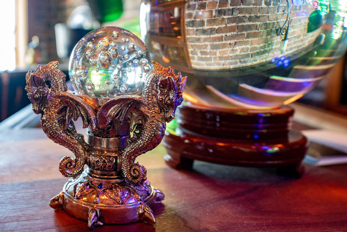 A closeup of a crystal ball framed with pewter dragons, next to a larger crystal ball.