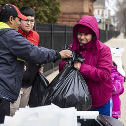 Estella Damien, 45, and her two children, 11-year-old Anthony Ora and 7-year-old Janelli Roa, receive three days of free breakfast and lunch meals for each student at William P. Nixon Elementary School, 2121 N. Keeler Ave., Thursday morning, March 19, 2020.