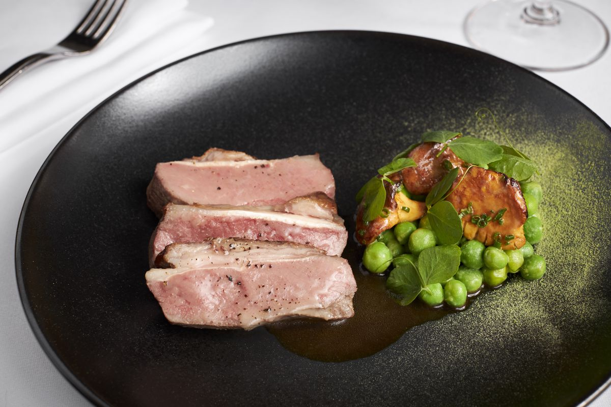A lamb dish at La Bise comes with chanterelle mushrooms and English peas that have been cooked in pea juice with herbs, preserved lemon, and a butter emulsion