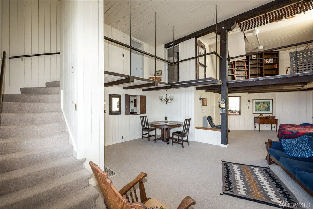 A high-ceilinged living area with stairs curving around the entire left wall leading up to a loft