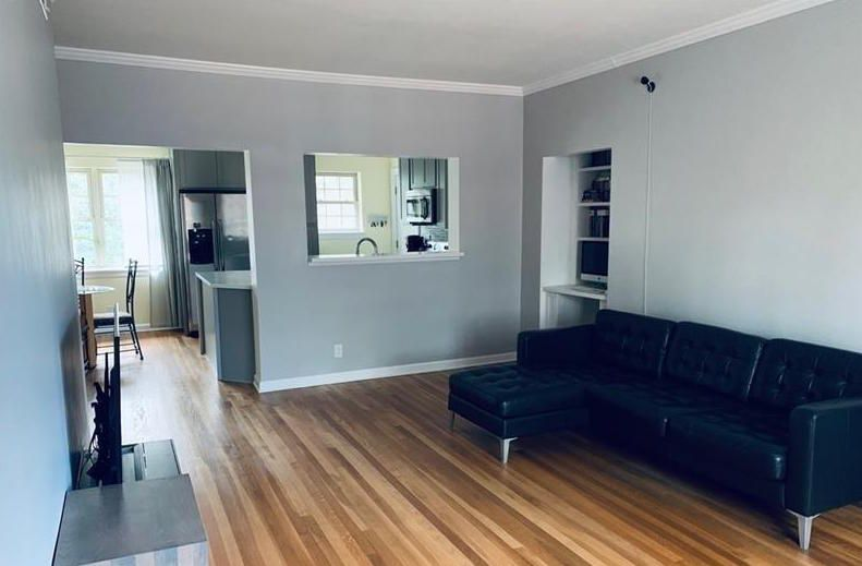 Living area with black couch and view of kitchen in the back.