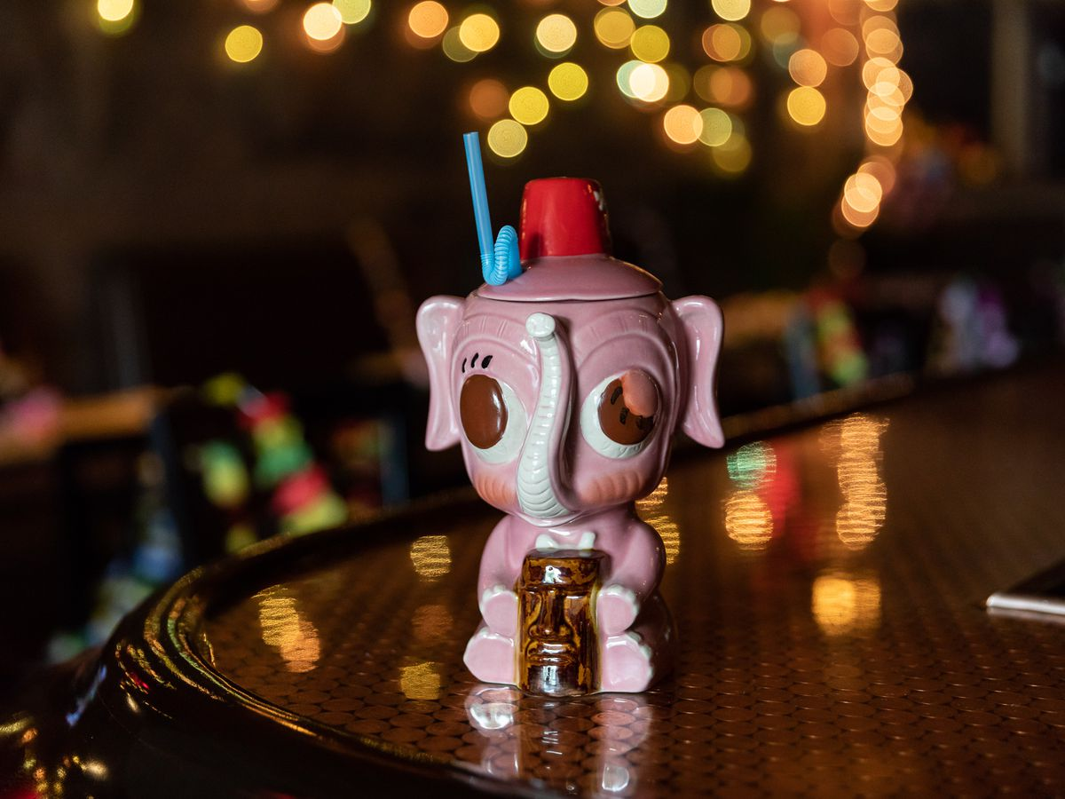 A tiki cocktail served in a pink elephant mug.