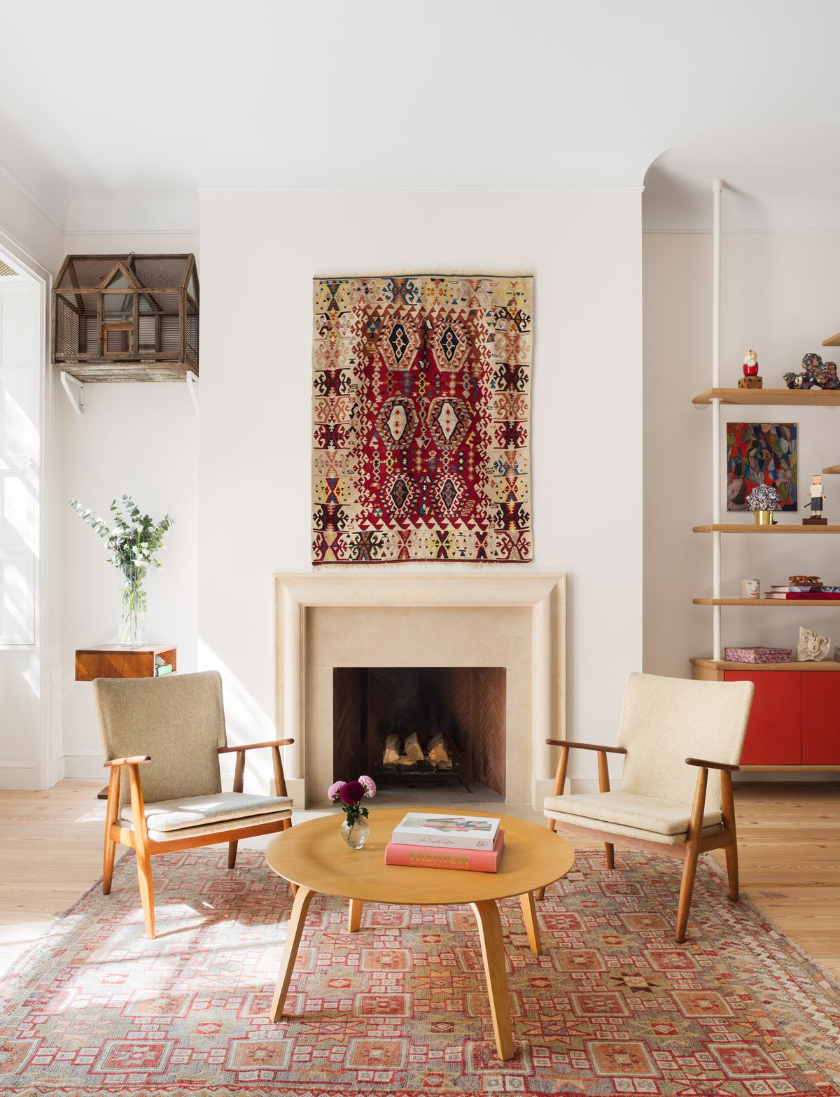 A living area. There is a fireplace. Over the fireplace hangs a patterned tapestry. In front of the fireplace are two tan chairs and a wooden coffee table. There is a patterned area rug under the table and chairs. There are shelves with objects next to th