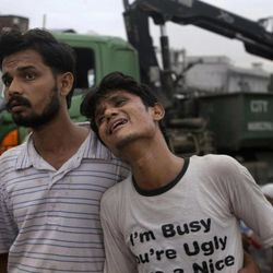 A Pakistani man comforts to another who weeps at the site of burnt garment factory in Karachi, Pakistan on Wednesday, Sept. 12, 2012. Pakistani officials say the death toll from devastating factory fires that broke out in two major cities has risen to 128. Hospital official Tariq Kaleem said the fire at a garment factory in the southern Pakistani city of Karachi killed 103 people. A blaze at a shoe factory in the eastern city of Lahore killed 25 people.