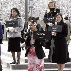 Sister missionaries display signs of their native languages to assist international visitors visiting Temple Square.