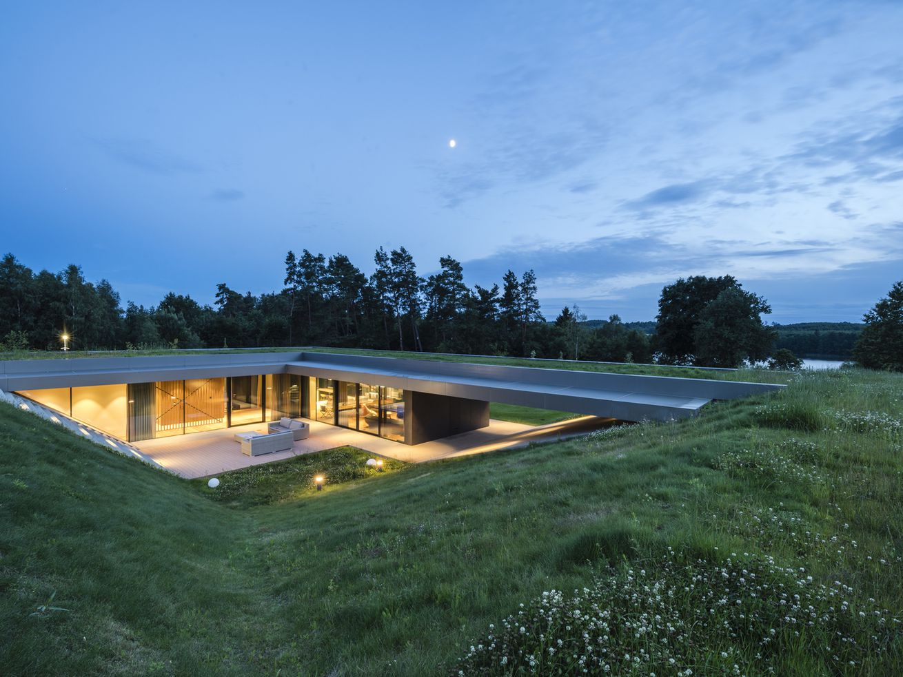 At the center of a grassy landscape is a sunken courtyard, which leads to glass walls enclosing living spaces lit up during dusk.