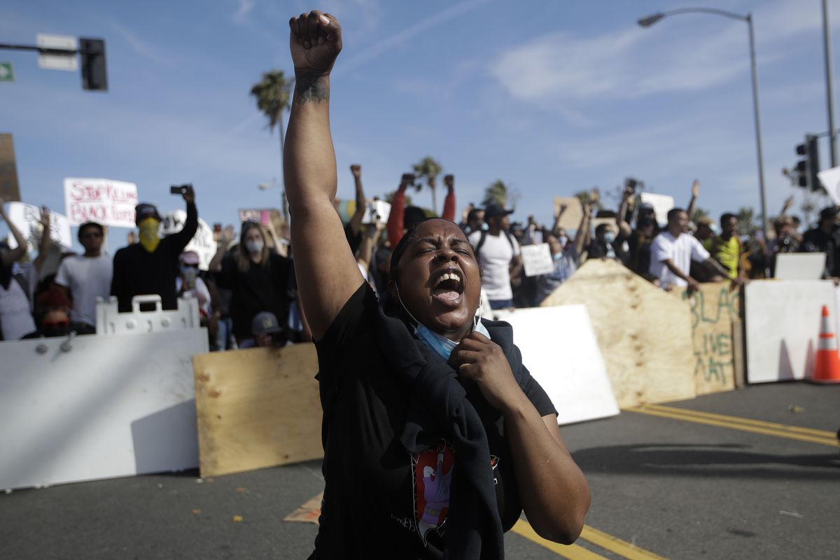 A protester yells Sunday, May 31, 2020, in Santa Monica, Calif. during unrest and protests over the death of George Floyd, a black man who was in police custody in Minneapolis. Floyd died after being restrained by Minneapolis police officers on May 25. (AP Photo/Marcio Jose Sanchez)