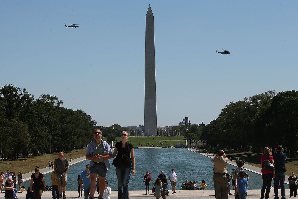Tourist Visit Lincoln Memorial As Marine One Carrying President Obama Flies Past