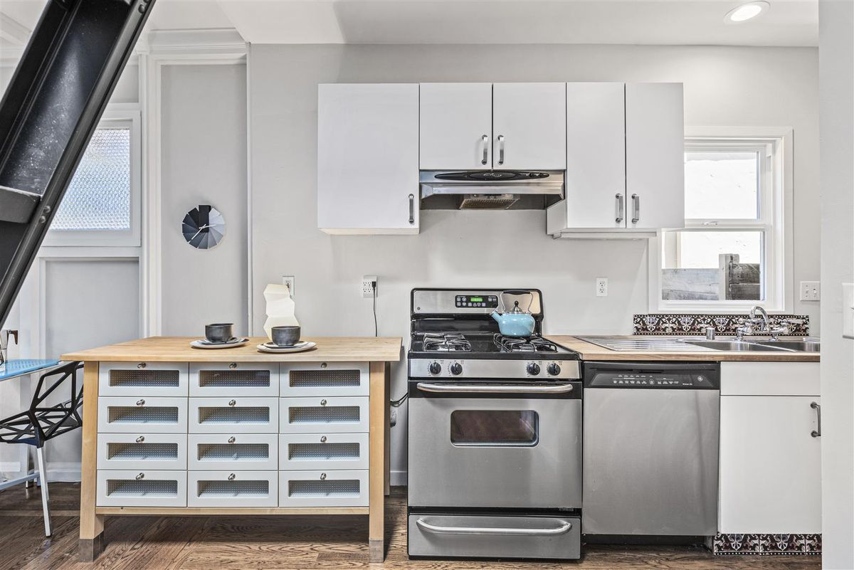 A kitchen with white cabinetry, a range and oven, stainless steel dishwater, and a small window.