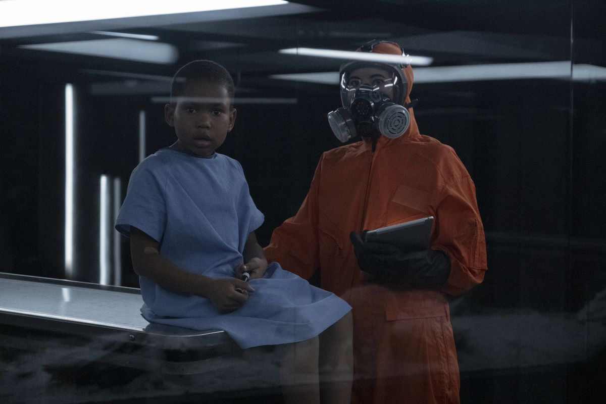 a boy in a blue hospital gown anxiously sits on a lab table, a figure in an orange biohazard suit stands over him. both look through a glass panel