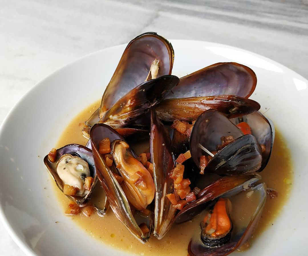 A bowl of cooked, open mussels in broth with bits of smoked fish, guanciale, and katsuobushi scattered on top