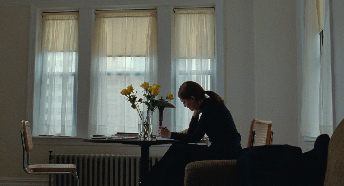 Francesca (Julianne Moore) writing at a table.