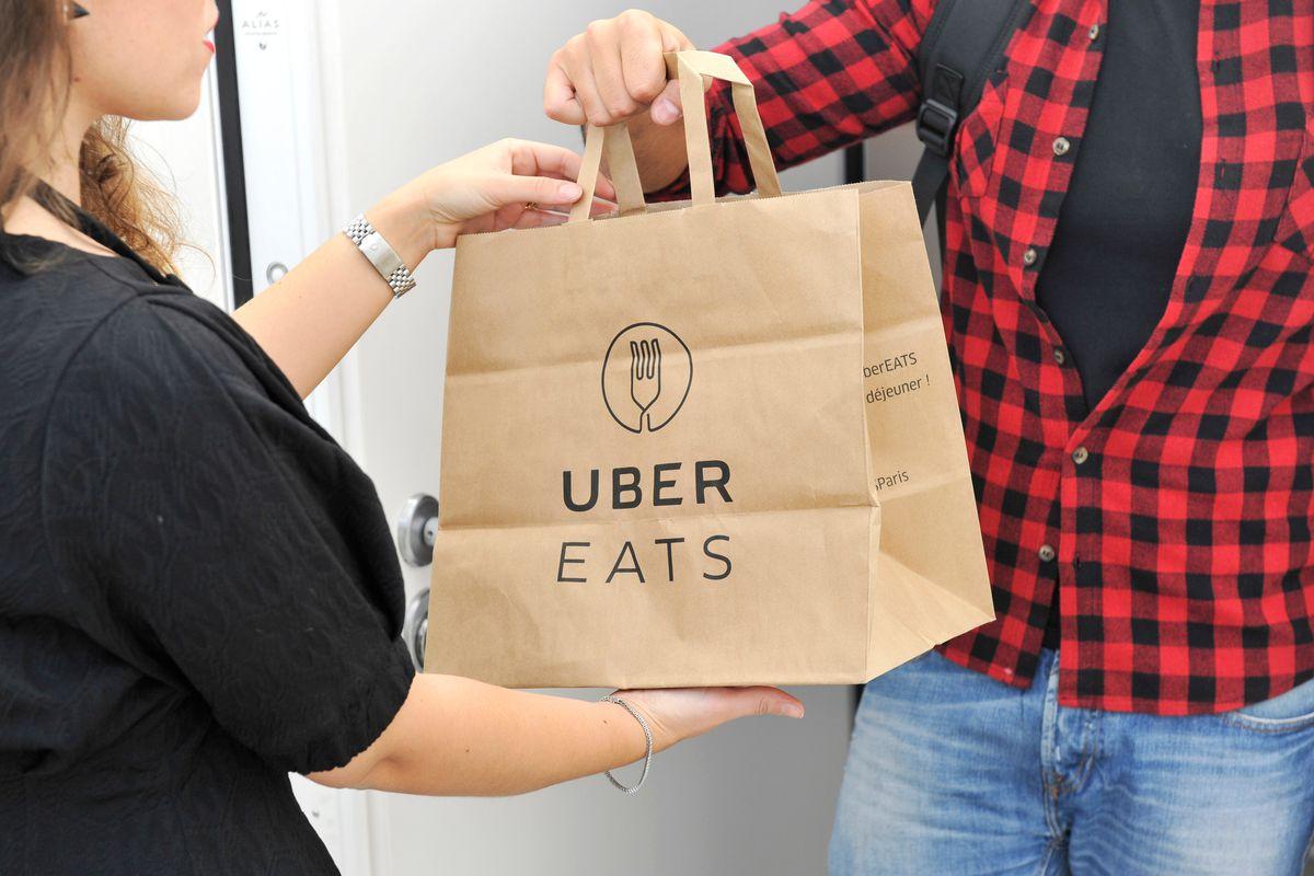 """一个优步吃送送一个红色的衬衫的送货员手拿一个纸袋,说""""优步吃""""给客户。"""