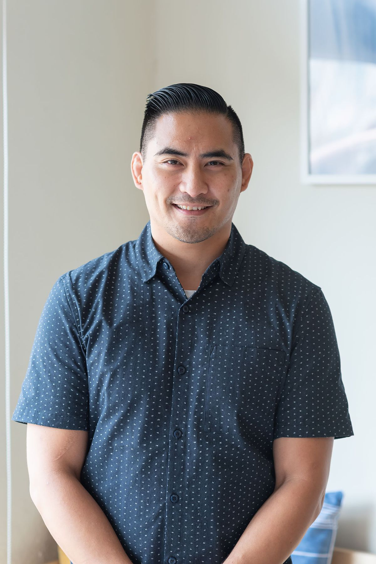 A portrait of chef Joseph Marcos standing in the light and smiling. He wears a blue polka dot shirt.
