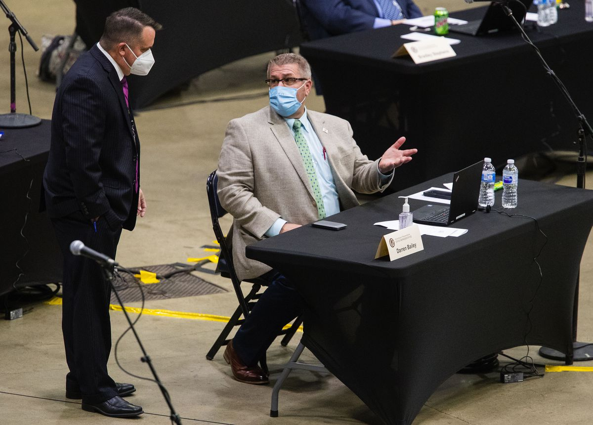 State Rep. Darren Bailey, R-Xenia, wears a face mask as he confers with a staff member at the Bank of Springfield Center in Springfield on Thursday.