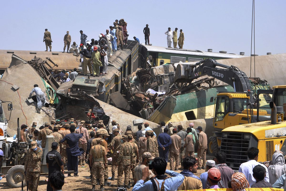 Soldiers and volunteers work at the site of a train collision in the Ghotki district in southern Pakistan, Monday, June 7, 2021. Two express trains collided in southern Pakistan early Monday, killing dozens of passengers, authorities said, as rescuers and villagers worked to pull injured people and more bodies from the wreckage.