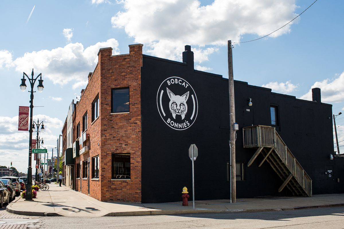 A brick building on the corner of two blocks. A logo of a cat is painted on the side.