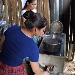 Magdalena Cuz and her daughter cook in a high-efficiency stove her family bought with help from the LDS Church.