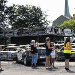 People take photos of a used car lot that was burned in downtown Kenosha during unrest overnight after police shot a Black man, Jacob Blake, in the the 2800 block of 40th Street, Monday morning, Aug. 24, 2020.