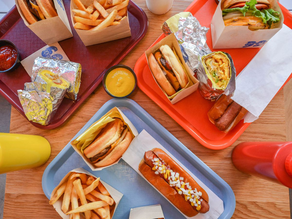 An overhead shot of colorful plastic trays holding burgers, fries, a breakfast burrito, and more.