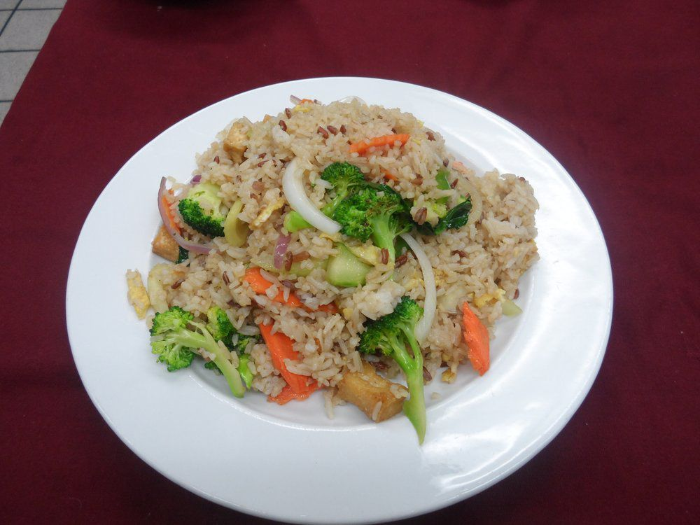 A close up image depicting a plate of fried rice with broccoli, onions, and carrots.