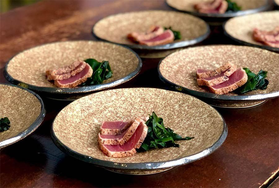 A dish of seared tuna on plates on a wooden counter