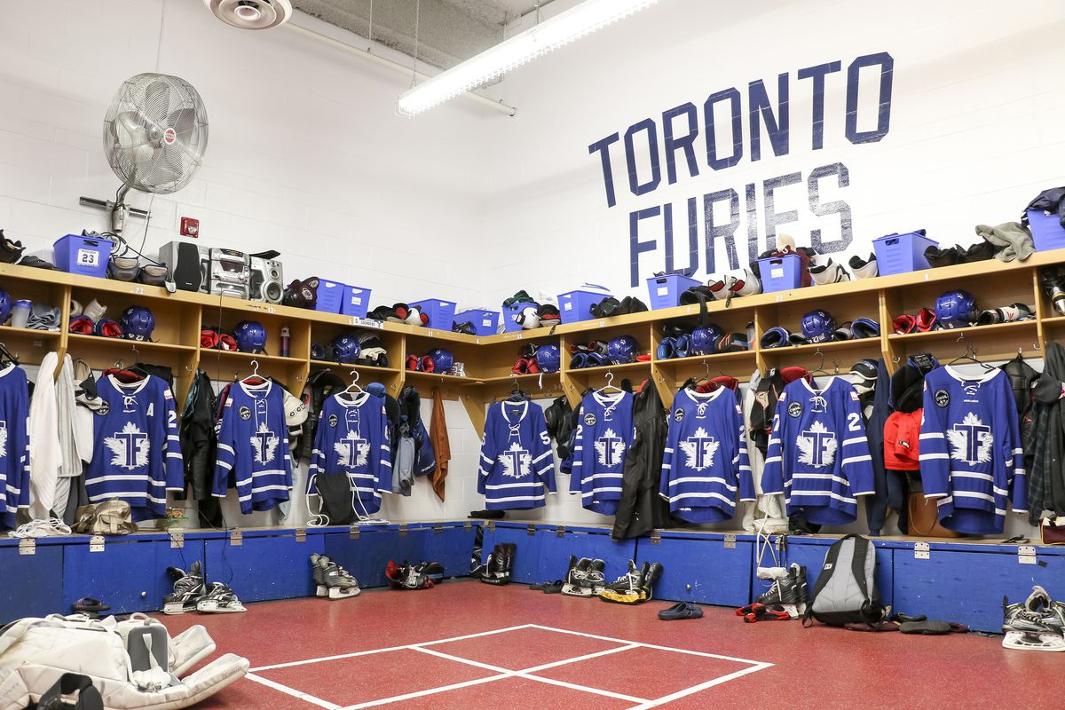 Toronto Furies locker room with player jerseys hung in every stall and other equipment ready to be worn.