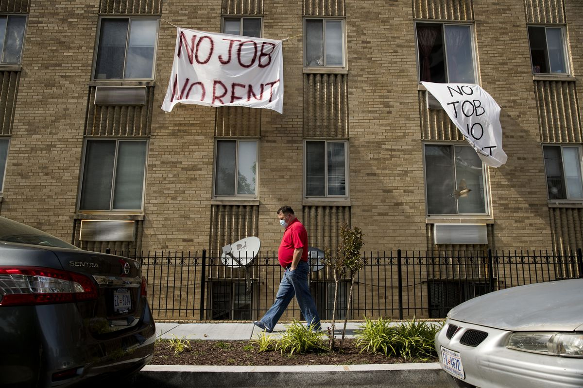 """Signs that read """"No Job No Rent"""" hang from the windows of an apartment building during the coronavirus pandemic in Northwest Washington."""