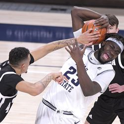 Utah State center Neemias Queta (23) grabs a rebound against Nevada forward Kwame Hymes, left, and guard Kane Milling during the first half of an NCAA college basketball game Sunday, Feb. 28, 2021, in Logan, Utah.