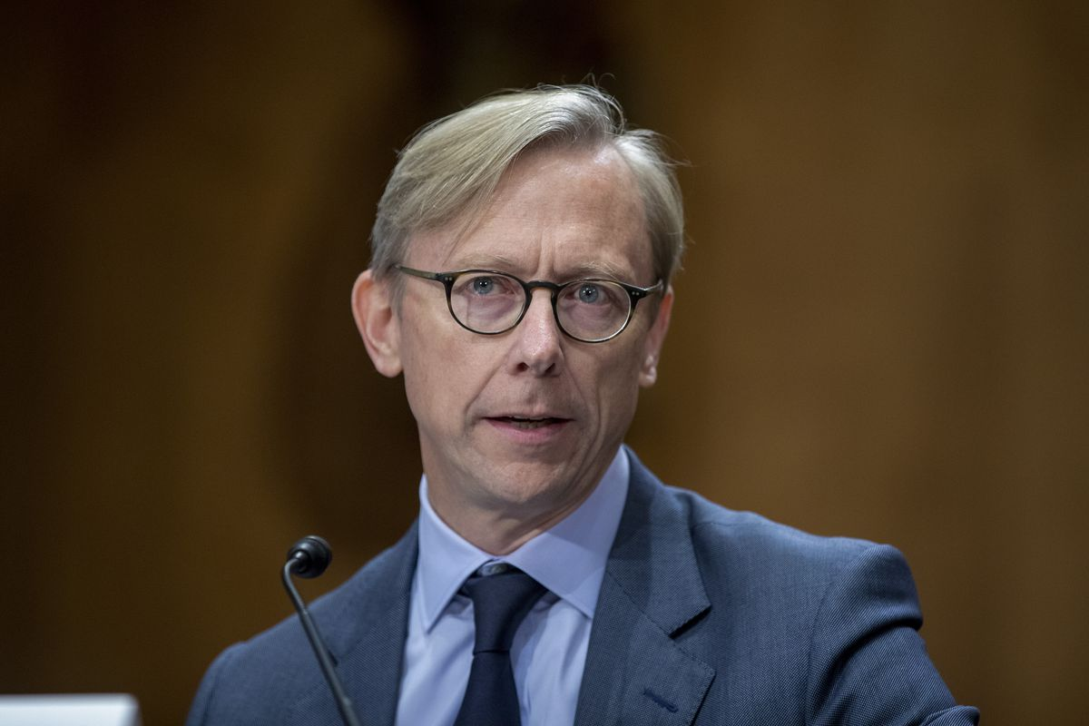 Brian Hook seated while speaking with committee members.