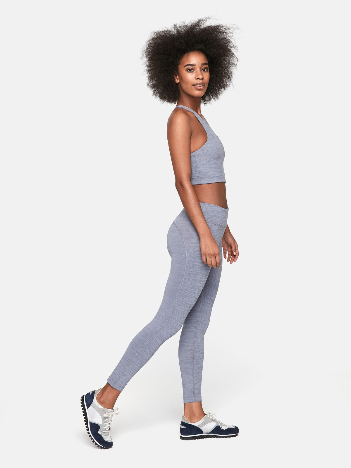 5f7011cc2 A model wears a gray-blue crop top and a matching pair of leggings.