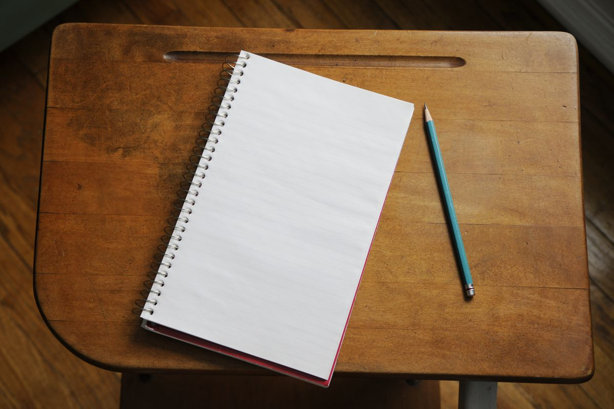 A notebook opened to a blank page next to a pencil on a wooden table