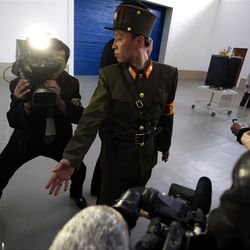 A North Korean soldier tries to keep order as journalists gather around the satellite that North Korean officials say will be launched with the country's Unha-3 rocket, slated for liftoff between April 12-16, as it shown to the media at Sohae Satellite Station in Tongchang-ri, North Korea on Sunday April 8, 2012. North Korean space officials have moved a long-range rocket into position for this week's controversial satellite launch, vowing Sunday to push ahead with their plans in defiance of international warnings against violating a ban on missile activity.(AP Photo/David Guttenfelder)