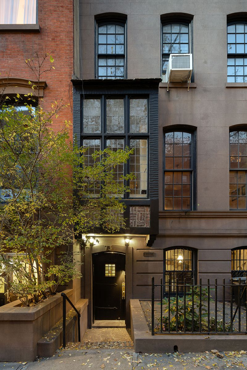 A brownstone facade with a bay window.