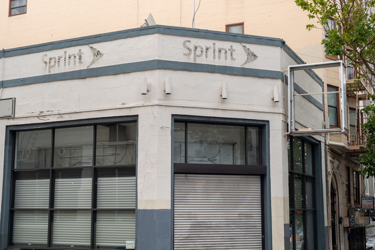 """A closed up shop corner with shutters in the window closed and the outline of """"sprint"""" on top."""