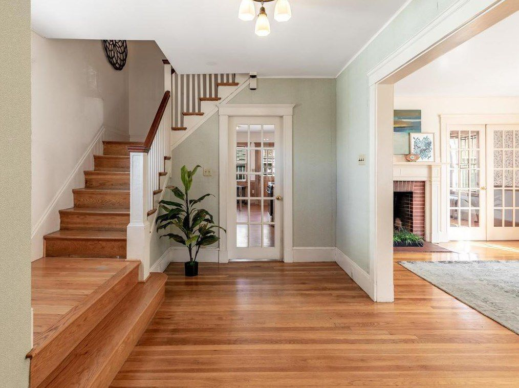 A spacious entry foyer with stairs and a single house plant.