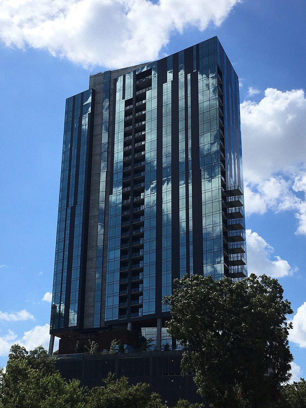 A tall glass building with trees grouped at the bottom