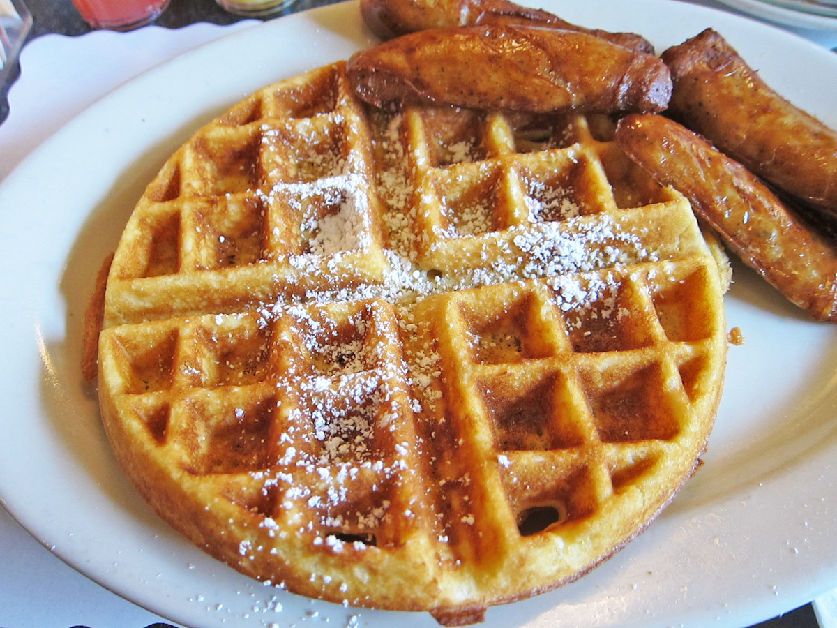 A white plate with a waffle on it along with some syrup