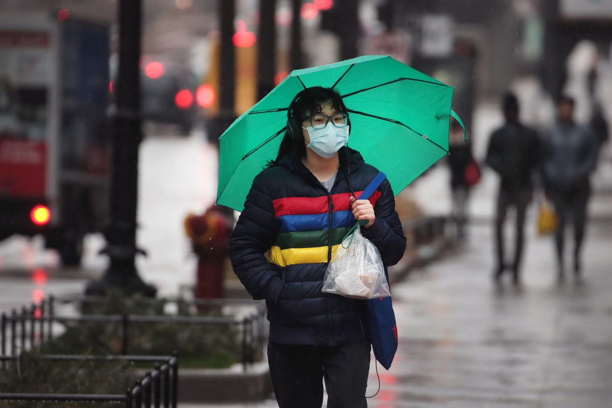 A woman wears a protective face mask while walking along Michigan Avenue on March 19, 2020.