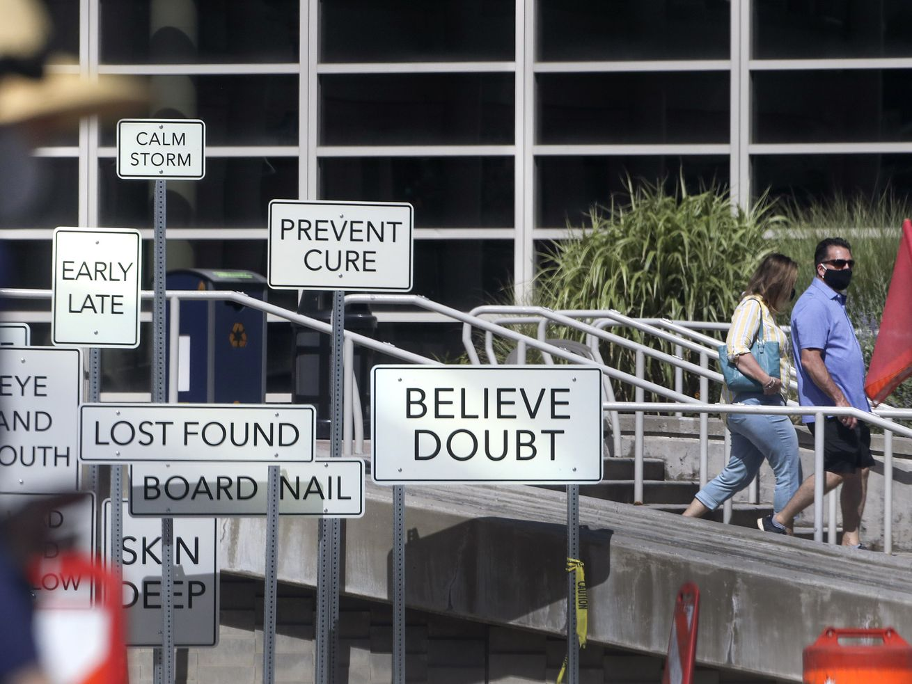 "Pedestrians wear masks as they walk past the ""Point of View"" art installation in front of the Salt Palace Convention Center in Salt Lake City on Monday, July 27, 2020. The installation, at West Temple and 100 South, was created by Maine artist Aaron T Stephan and features over 150 road signs with diametrical words on them."